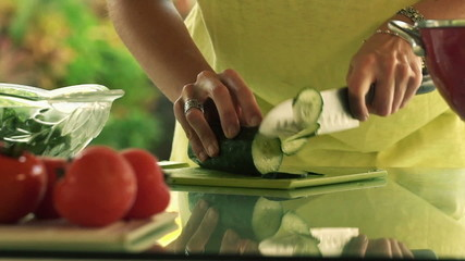 Woman hands slicing cucumber in kitchen, slow motion