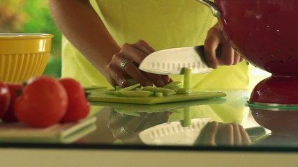 Woman hands slicing cucumber in kitchen, slow motion shot at 120