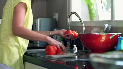 Woman hands washing salad in kitchen at home