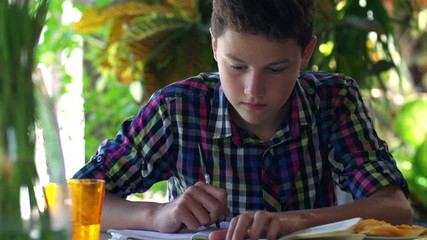 Young teenager doing homework, writing notes in notebook at home