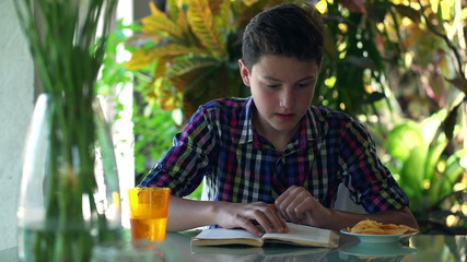 Teenager reading book by the table at home