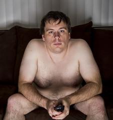 Obese naked man watching TV