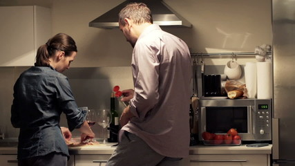 Young couple cooking, adding seasoning on raw meat in kitchen