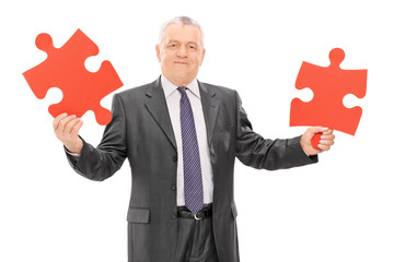 Mature businessman holding two pieces of a puzzle