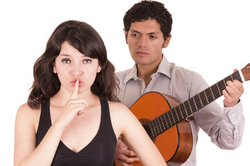 beautiful girl gesturing silence while young man serenades her