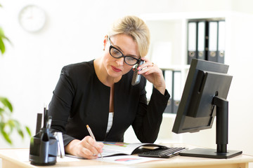 middle-aged business woman working in office and talking on