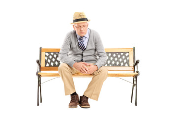 Sad senior thinking seated on a bench