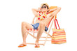 Young man enjoying seated in a sun lounger
