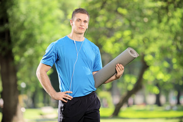 Young athlete holding a mat and listening to music