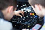 Mechanics at repair shop working on a car engine - 75360822