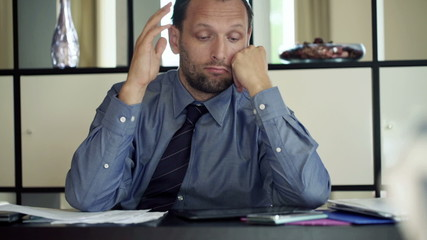 Bored young businessman sitting by the desk at home