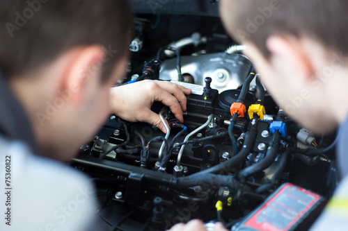 Mechanics at repair shop working on a car engine - 75360822