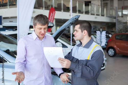 An angry customer talking to a mechanic in auto repair service - 75360828