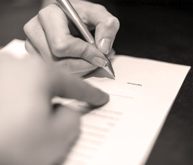 Hands of two people signed the document. Black white