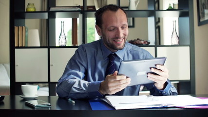 Successful businessman with tablet computer in office