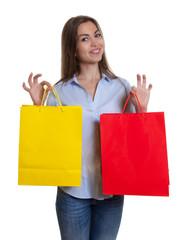 Lachende Frau mit braunen Haaren und Einkaufstaschen