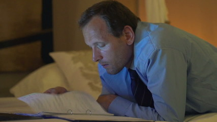 Young businessman reading documents, lying on bed late at night