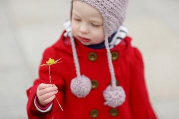 Little girl holding straw flower on Easter