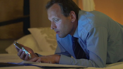 Businessman comparing data on smartphone and documents on bed