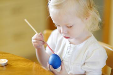 Adorable little girl coloring an Easter egg
