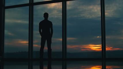 The man stands by sky scraper business center windows