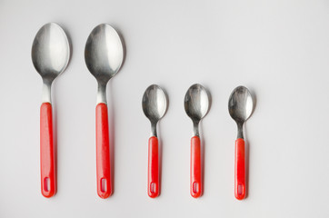 family of two large spoons and three small teaspoons
