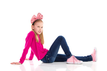 Sitting girl with a pink hair bow.