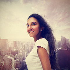 Smiling young Indian woman against a cityscape