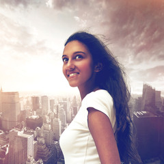 Pretty young Indian woman on a city background