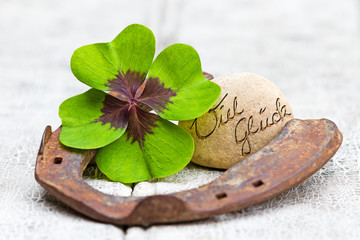 Glücksbringer und Stein auf Holz, Viel Glück