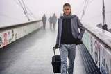 Fototapety Trendy handsome man walking with a suitcase