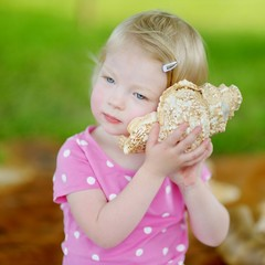 Cute little toddler girl with a shell