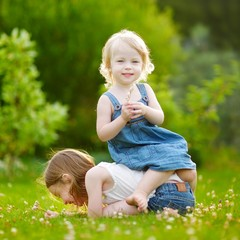 Two sisters having fun while sitting on the grass