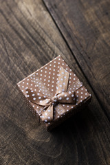 Gift box with ribbon ornament on wooden background.