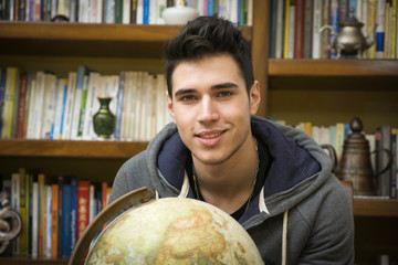 Handsome young man holding a globe indoors