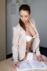 Sexy secretary sitting on desk and write