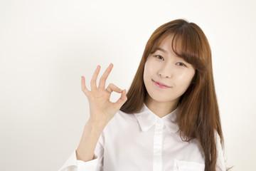Beautiful asian female student giving okay sign