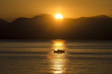 Sunset, lake sparkling.Fishermen driving a small fishing boat