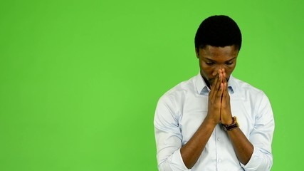 young handsome black man prays - green screen