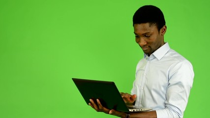 black man works on notebook and smiles - green screen - studio