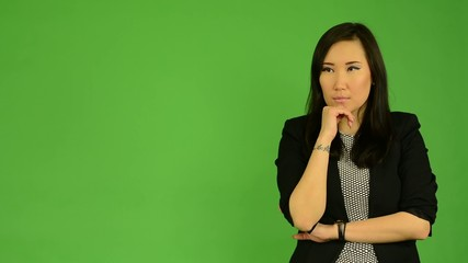 young attractive asian woman thinks - green screen