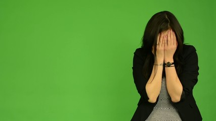 young attractive asian woman cries - green screen