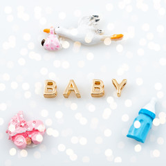 Golden word baby on white with tiny toys. Pacifier, pram, bird