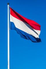Netherlands flag on the blue sky