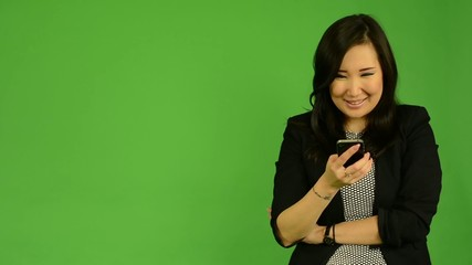 asian woman works on smartphone and smiles -green screen