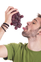 Guy licking bunch of grapes