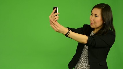 asian woman photographs with smartphone (selfie) - green screen