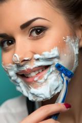 Cute brunette in hair curlers posing with razor on blue backgrou
