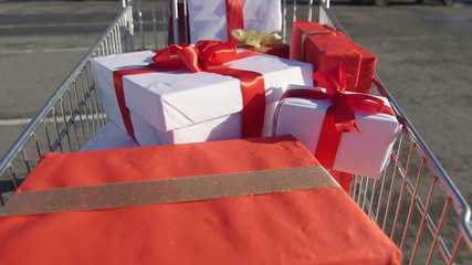 Shopper pulling shopping trolley full of gift boxes