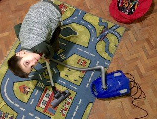 Child clean nursery with vacuum cleaner